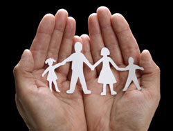 A picture of a person holding a white paper cutout of a a family in their hands.